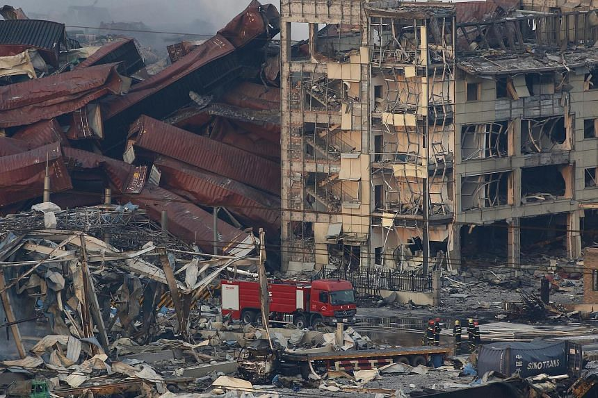 Firemen working among several destroyed buildings and containers after a huge explosion rocked the port city of Tianjin, China, on Aug 13, 2015.