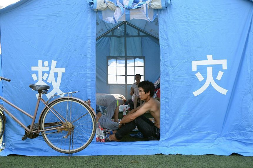 Victims of the massive explosions sitting in a tent in a temporary shelter at an elementary school in Tianjin on Aug 13, 2015.