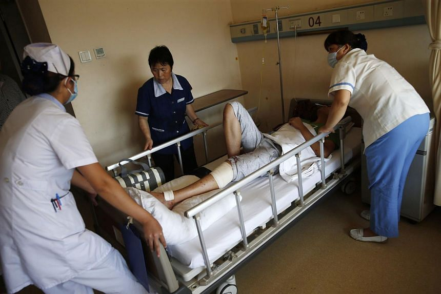 Medical personnel taking care of a victim of the explosions as the latter lies on a hospital bed in Tianjin on Aug 13, 2015.