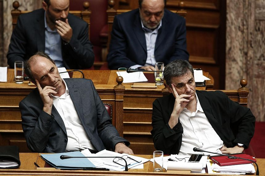 Greece's Finance Minister Euclid Takalotos (right) and Economy Minister George Stathakis during a parliamentary session ahead of a vote by lawmakers on a bailout deal on Aug 13.