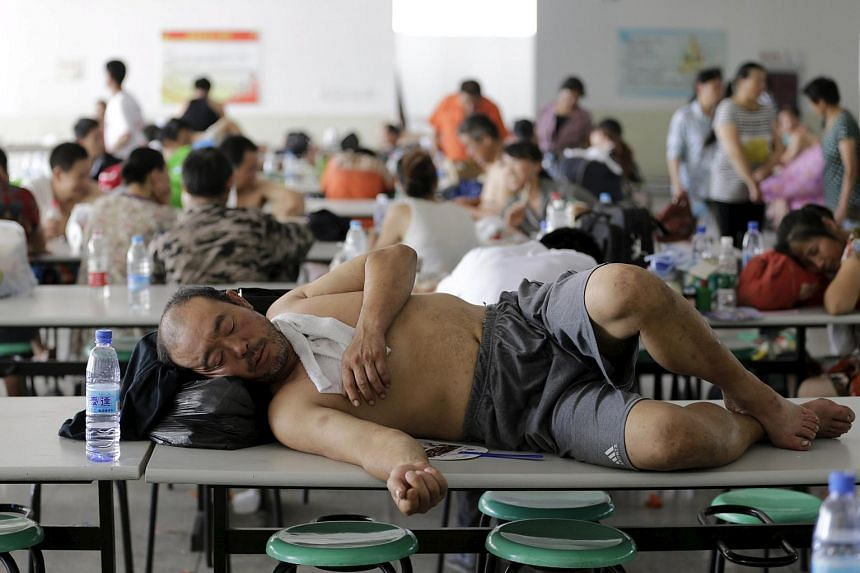 A man resting on a table at a primary school dining hall, which has been turned into a shelter, in Tianjin on Aug 13.