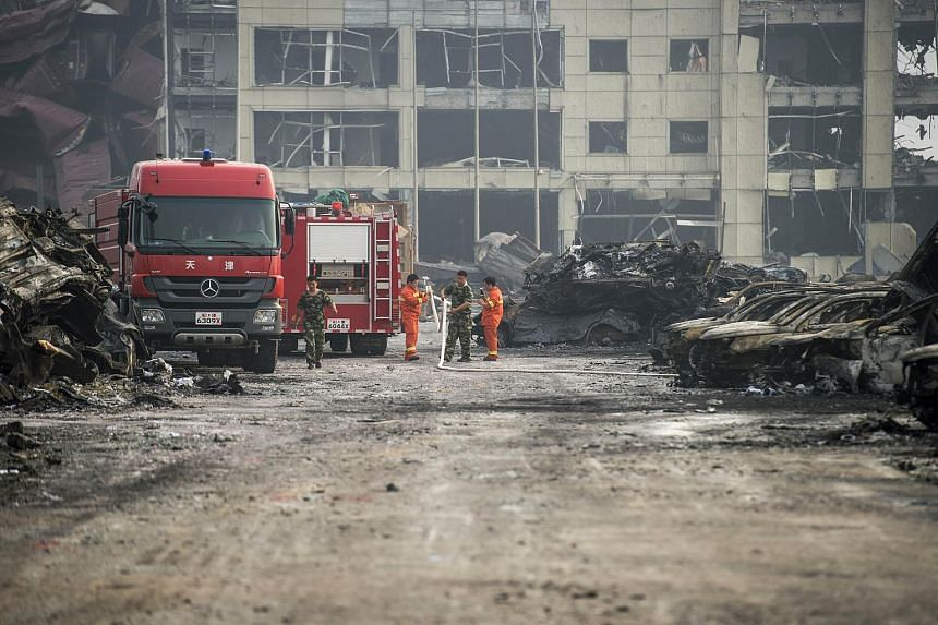 Chinese firefighters working in Tianjin on Aug 14, the second morning after a series of explosions at a chemical warehouse hit the city.