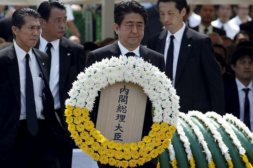 Japan's PM Shinzo Abe offering a wreath during a ceremony marking the 70th anniversary of the Nagasaki bombing, on Aug 9.