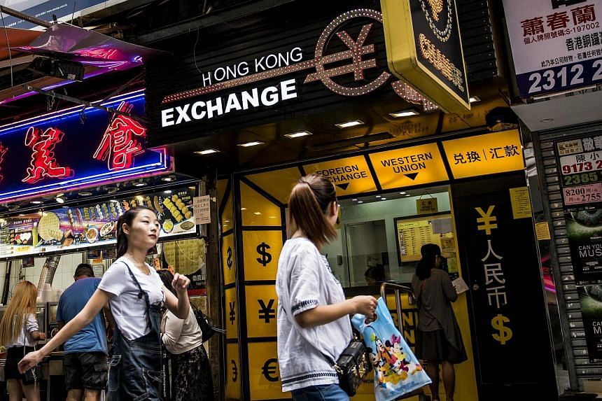 Pedestrians walking past a currency exchange in Hong Kong on Aug 12.