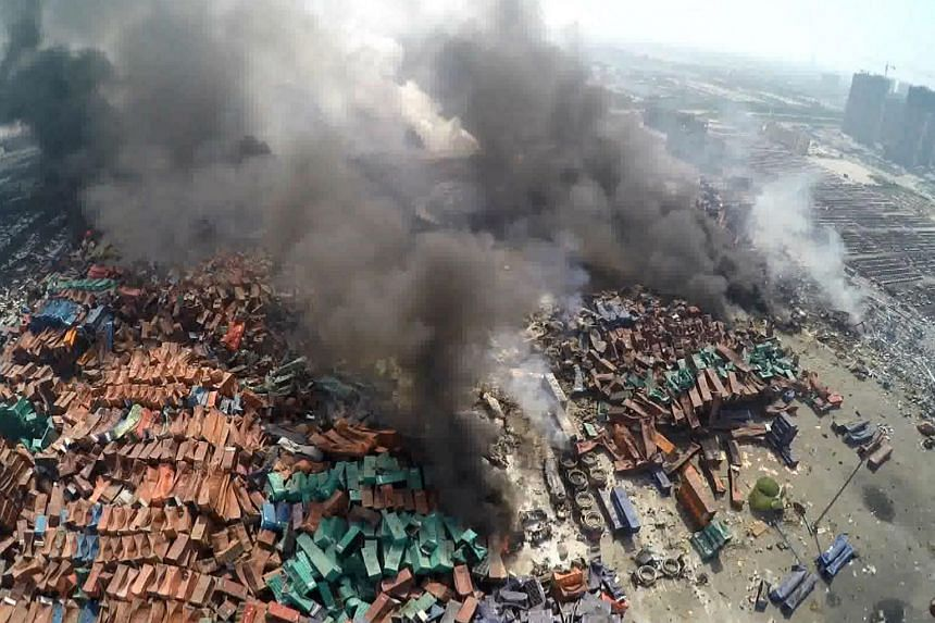 This screen grab taken from AFPTV shows an aerial image of smoke rising from debris the day after a series of explosions hit a chemical warehouse in the city of Tianjin, in northern China.