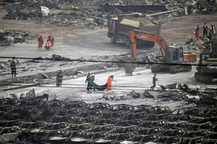 Firefighters carrying the body of a victim from the site of the explosions in Tianjin, China, on Aug 14, 2015.