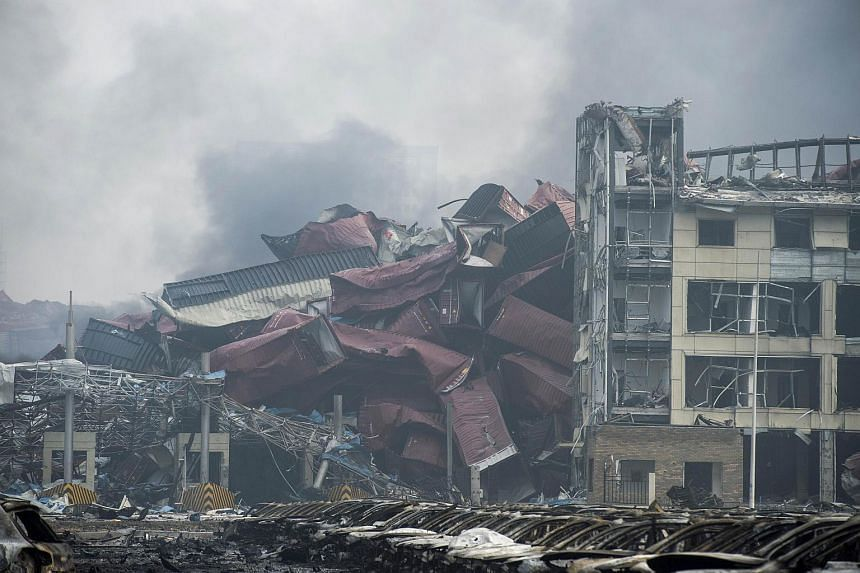 Shipping containers sit piled up next to a badly damaged building on the second morning after a series of explosions at a chemical warehouse hit the city of Tianjin, China on Aug 14, 2015.
