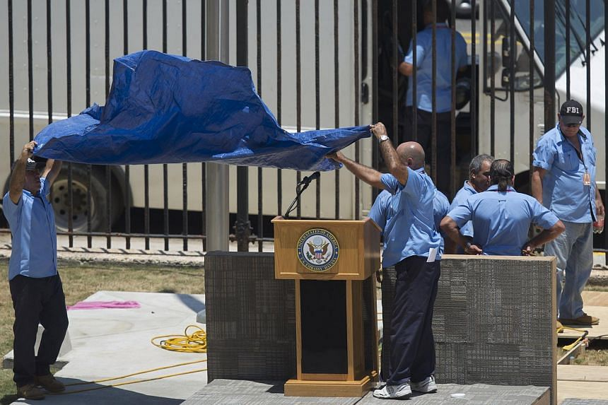 Workers covering a podium with the seal of the US embassy in Havana on Aug 13.