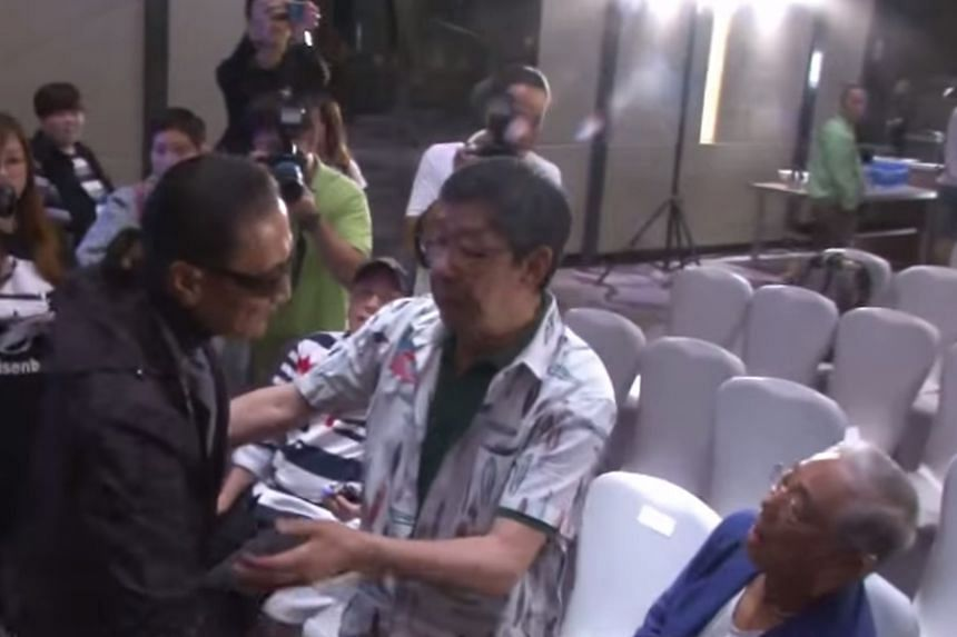 Wu Fung (centre) intervening after Patrick Tse (left) tries to slap Kenneth Tsang (right) at a publicity event for their reality travel show. Wearing a cap and seated behind is Joe Junior.
