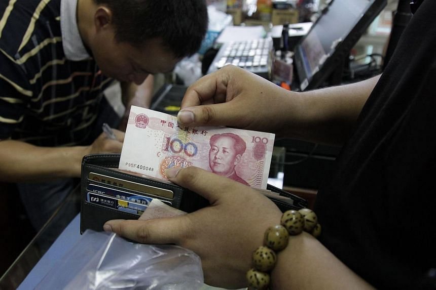 A man with a 100 Chinese yuan note at a convenience store in Beijing.