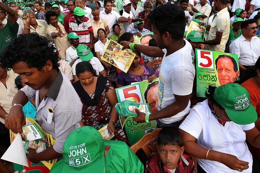 Workers for the United National Party of Prime Minister Ranil Wickremesinghe handing out election material during a rally in Colombo. Pundits expect the ruling reformist alliance to win a majority in Monday's election.
