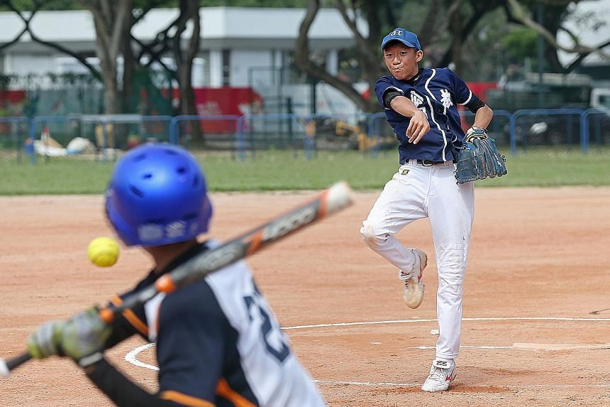 Catholic High School's Aloysius Ong (right) pitches in the Schools National Boys' softball C Division final against St Gabriel's Secondary. Catholic High won 9-3 to take the title for the first time since 2009.
