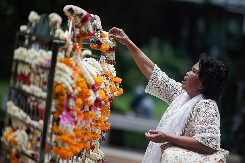 A Thai woman praying for the health of King Bhumibol Adulyadej outside Siriraj Hospital in Bangkok yesterday. The 87-year-old Thai king, the world's longest-living monarch, is recovering after treatment for water on the brain, or hydrocephalus, and a