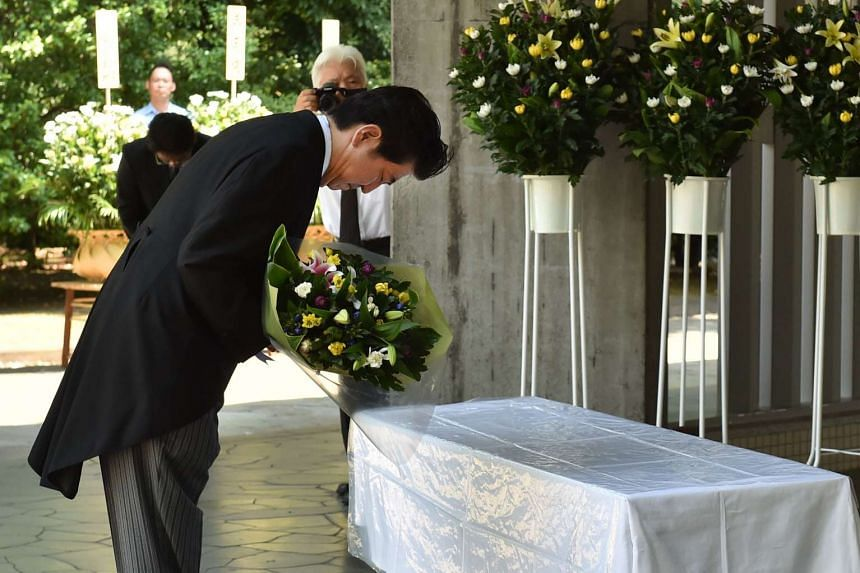Japan's Prime Minister Shinzo Abe offers a bouquet of flowers during a visit to the Chidorigafuchi National Cemetery for unknown war victims in Tokyo on August 15, 2015 to offer prayers during commemorations marking the end of World War II.