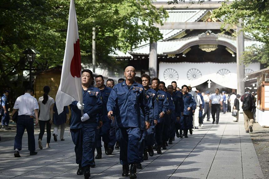 Japanese right-wing group members parade after they offered prayers at the controversial Yasukuni Shrine in Tokyo on August 15, 2015, the day of the 70th anniversary of the end of World War II. --