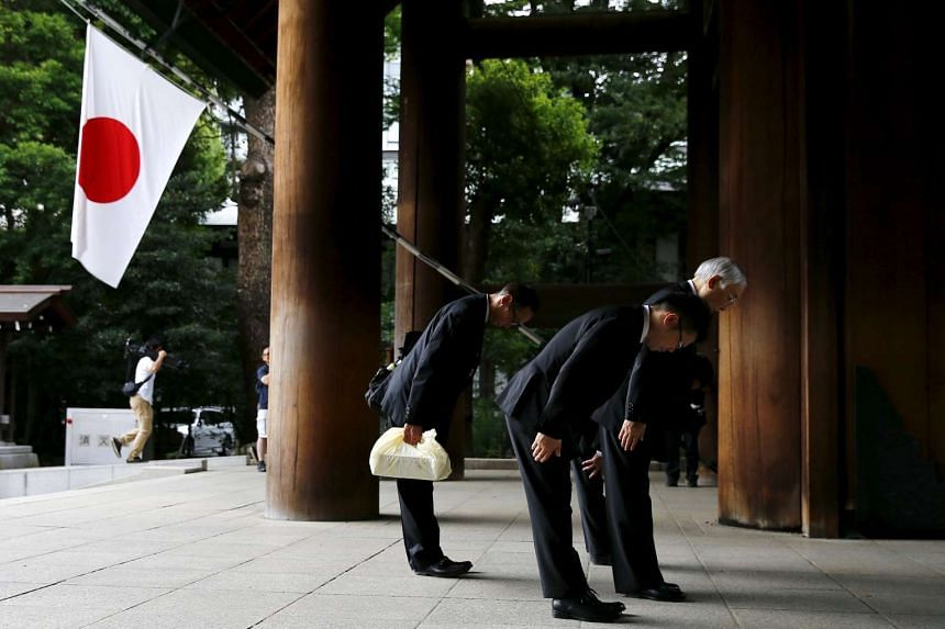 Men bowing before entering Yasukuni Shrine on the anniversary of Japan's surrender in World War Two in Tokyo on Aug 15, 2015.