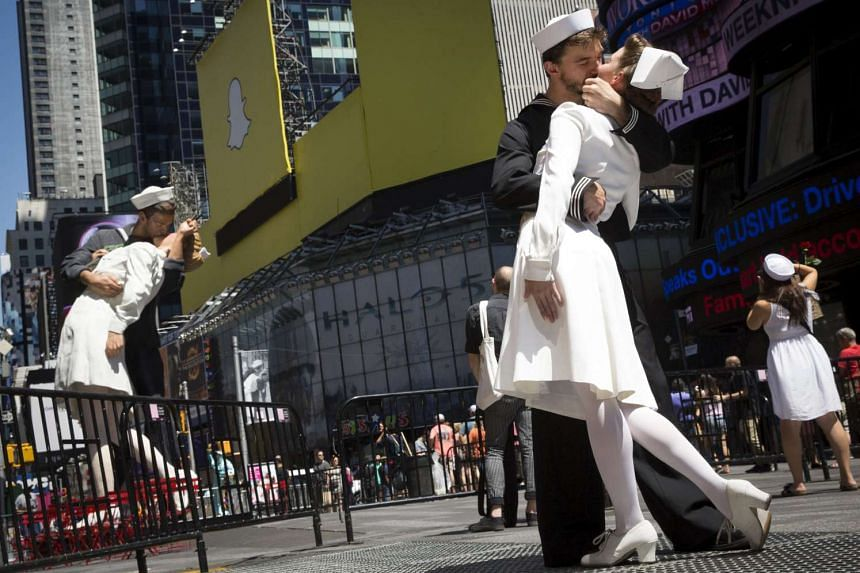 Actors reenact the famous picture of a sailor kissing a nurse, near a replica sculpture in New York's Times Square.