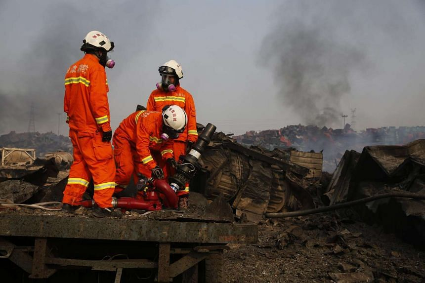 Firemen wearing gas masks prepare to combat fresh fires in the area of a huge explosion that rocked the port city of Tianjin, China.