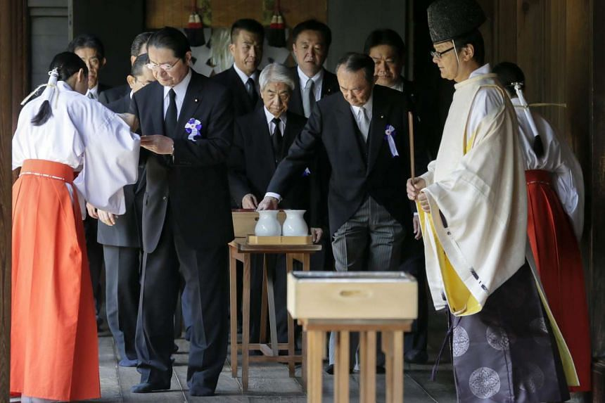 Japanese lawmakers are served sacred sake by shinto attendants after offering ritual prayers at Yasukuni Shrine on Aug 15, 2015.
