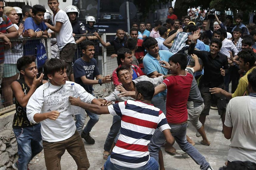 Pakistani, Iranian and Afghani migrants scuffle over their priority in a registration queue on Kos.