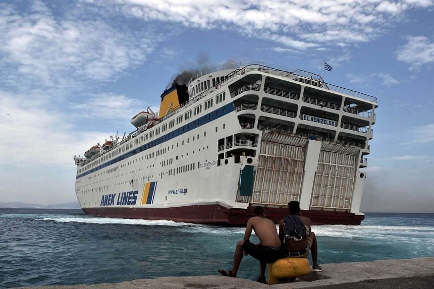 Migrants watch the arrival of the Eleftherios Venizelos ferry at the port of Kos.