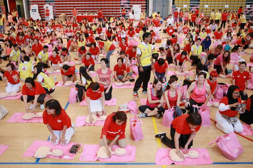 Women learning how to perform CPR during the People's Association Women's Integration Network (WIN) Council Zumba fitness party at ITE College Central on Aug 16, 2015.