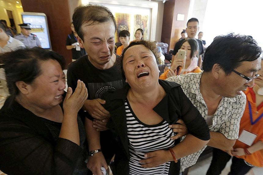 The mother of a missing firefighter being helped by family members as they wept outside the venue of a news conference in Tianjin.