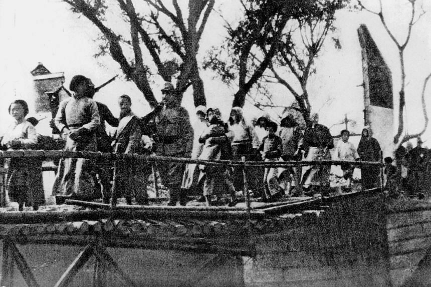 """Japanese soldiers taking civilian women away during the Nanjing (Nanking) Massacre in 1937. """"Comfort women"""" from countries such as South Korea, China and the Philippines were forced to work in Japanese military brothels during the Second World War."""