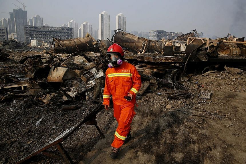A fireman wearing a gas mask searching the site of the giant chemical explosions in the Chinese port city of Tianjin. Police confirmed for the first time yesterday that there was highly-poisonous sodium cyanide chemical at the site of the warehouse b