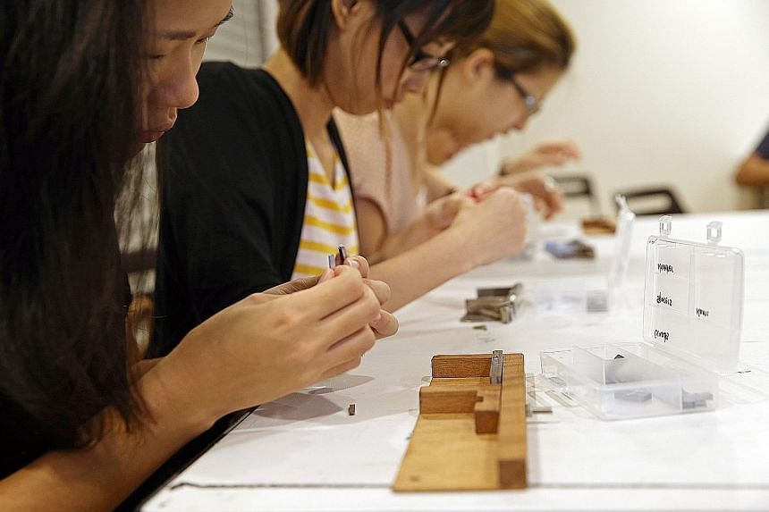 Participants painstakingly putting metal types on a composing stick to make name cards at a hands-on workshop. Titled Printing From The Past: Letterpress And Typesetting, it gave an introduction to letterpress printing and basic typesetting, the tool