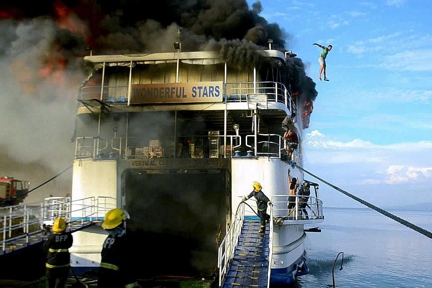 A crew member jumping off the ferry Wonderful Stars after it caught fire at the port in Ormoc city, central Philippines, yesterday. All 544 passengers were evacuated safely. More than a month ago, 61 passengers were killed when the Kim Nirvana ferry