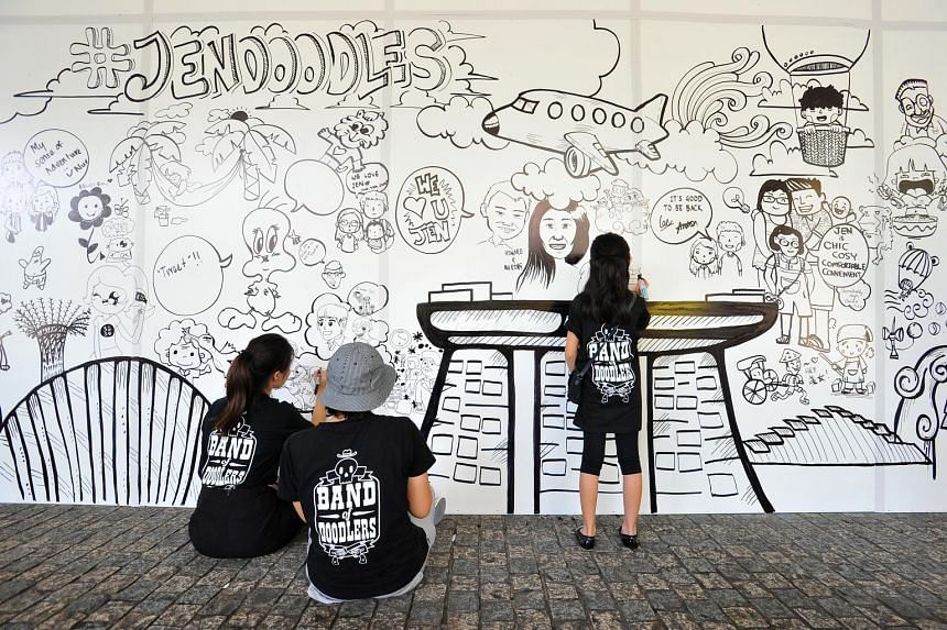 """It brings a whole new meaning to the term """"drawing room"""". A group of local artists, The Band of Doodlers, were invited to Hotel Jen, off Tanglin Road, yesterday to transform a 17m-wide hoarding into a work of art while renovation work was being done"""