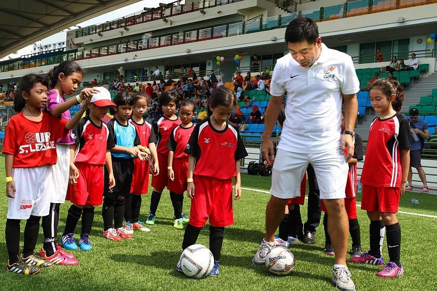 Football Association of Singapore vice-president Bernard Tan joining children aged between six and 12 at the launch of the FAS Grassroots Cubs programme at the Jalan Besar Stadium yesterday. The kids took part in various coaching stations promoting f