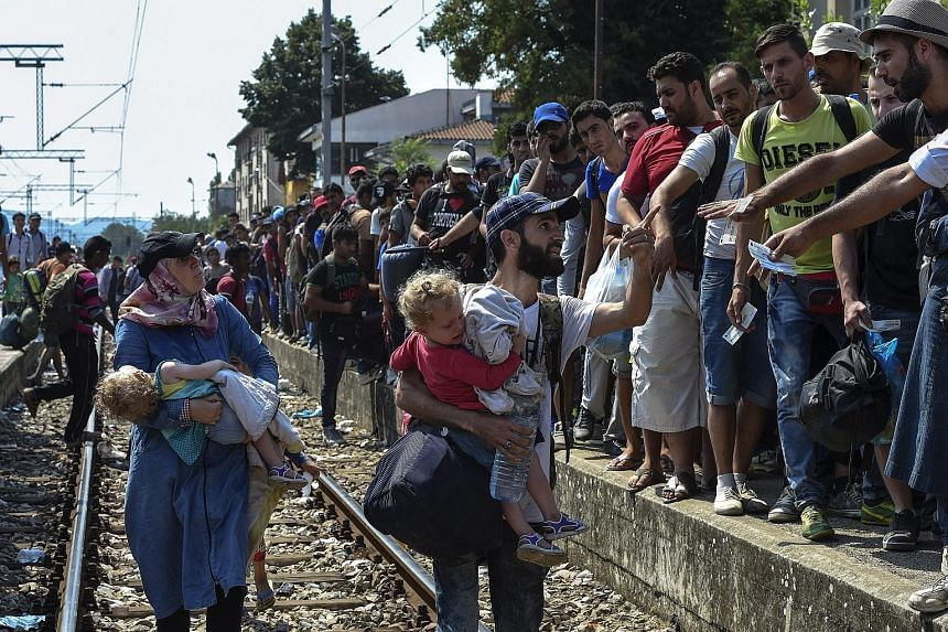 Migrants with their children trying to pass the line and get in a train heading to the Serbian border at the train station in Gevgelija yesterday. Macedonia says it is doing everything it can to deal with the refugee problem, but the scale of the cri