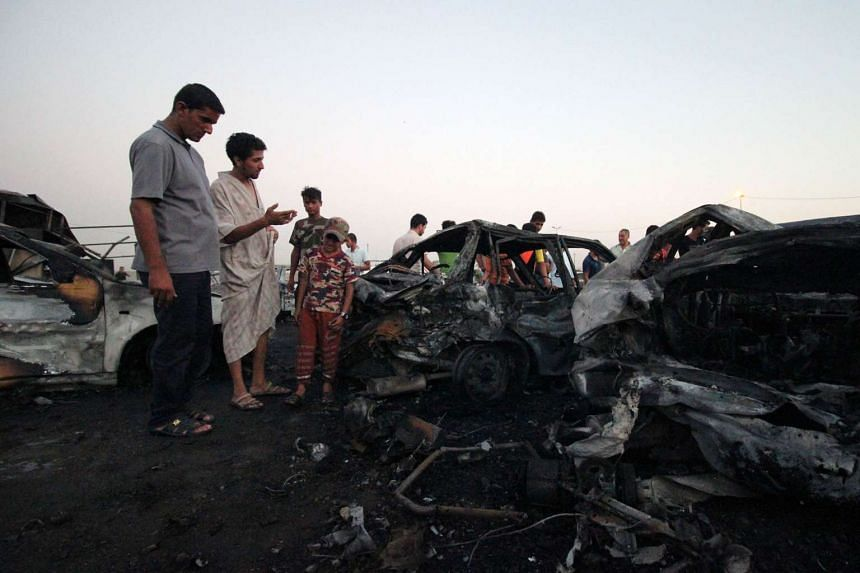 Iraqis look at the damage caused by the car bombing.