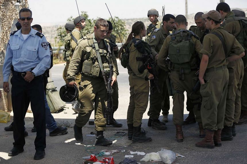 Israeli security forces stand at the site where a Palestinian was shot and wounded by Israeli troops after he had stabbed a soldier.