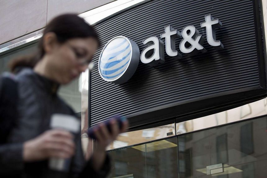 A pedestrian looks at a mobile phone while walking past an AT&T Inc. store in Washington, DC, US.