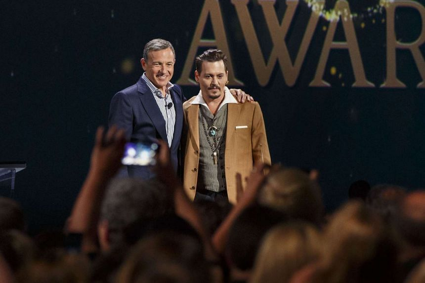 """Robert """"Bob"""" Iger, chief executive officer of The Walt Disney Co., left, stands for a photograph with actor Johnny Depp as he honored during the Disney Legends Awards at the D23 Expo 2015 in Anaheim, California, US, on Aug 14, 2015."""