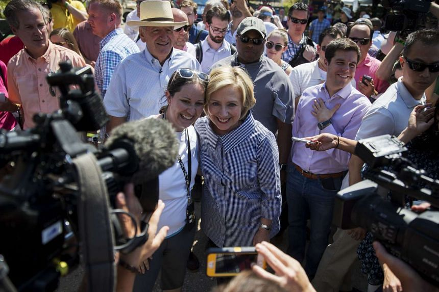 "Hillary Clinton, former U.S. secretary of state and 2016 Democratic presidential candidate, takes a photograph ""selfie"" with an attendee while touring the Iowa State Fair in Des Moines, Iowa, US, Aug 15, 2015."