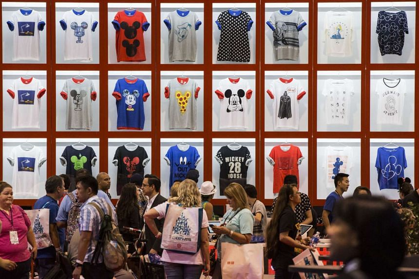 People shop for Walt Disney Co.'s Mickey Mouse themed graphic t-shirts from Uniqlo Co. during the D23 Expo 2015 in Anaheim, California, US, on Aug 14, 2015.
