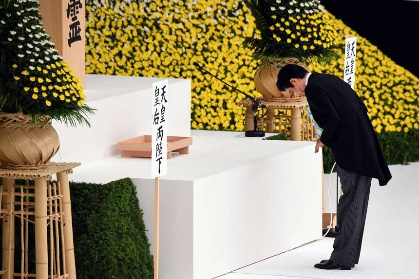 Japan's Prime Minister Shinzo Abe bowing before placing a flower on an altar during an annual memorial service for war victims in Tokyo on Aug 15, 2015. Japan marked the 70th anniversary of the end of the World War II on August 15 under criticism fro