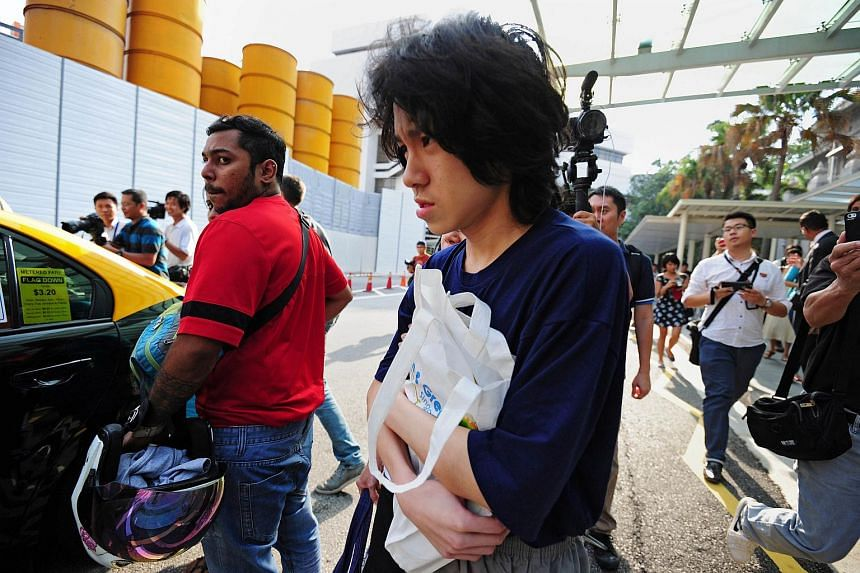 Singapore teenage blogger Amos Yee (center) is surrounded by members of the media after walking out from the state court in Singapore on July 6, 2015.