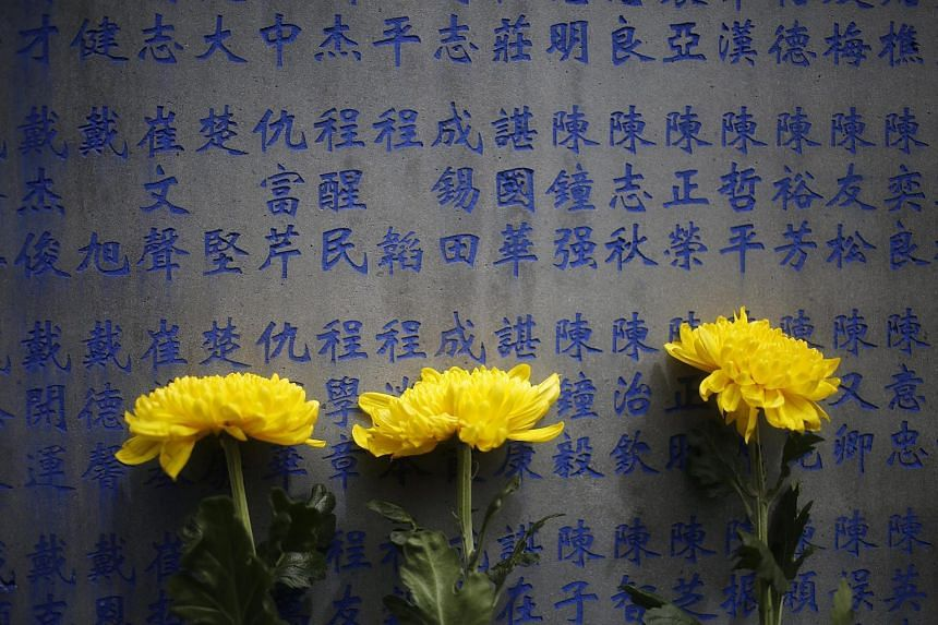 Flowers are placed against a wall with the names of Chinese soldiers killed during WWII at the Tengchong Graveyard of National Heroes in Yunnan province, China, on Aug 13 2015.