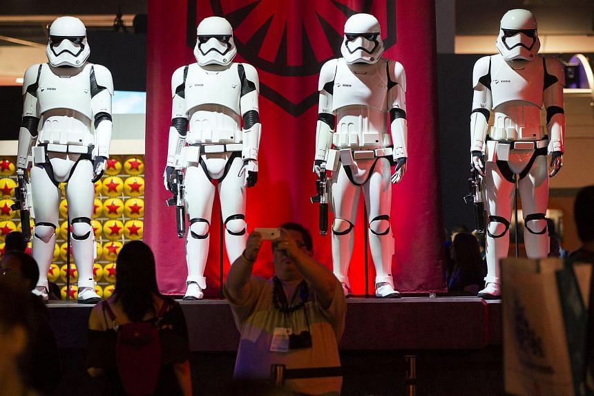 An attendee takes picture with Stormtroopers costumes from the Star Wars franchise during the D23 Expo 2015 in Anaheim, California, US, on Aug 14, 2015.