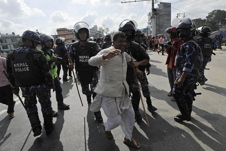 Nepalese police arrest an opposition supporter during a general strike called by the 30-party alliance led by a hardline faction of former Maoist rebels against the draft of the new constitution, in Kathmandu on Aug 16, 2015.