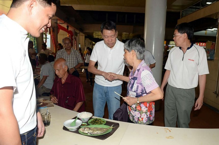 Former senior police officer Melvin Yong shaking hands with people during a walkabout at Pek Kio market.