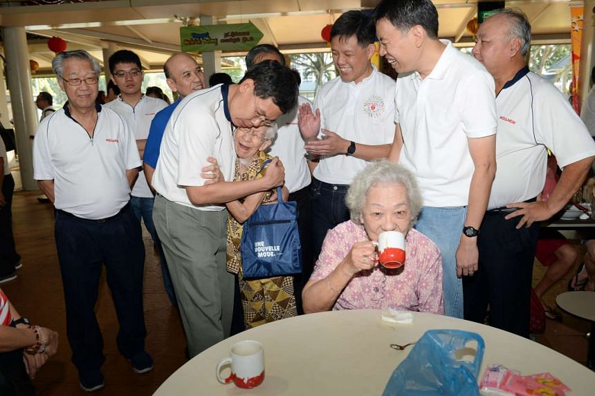 Transport Minister Lui Tuck Yew hugging Mdm Koh ,85, during a walkabout at Pek Kio market.