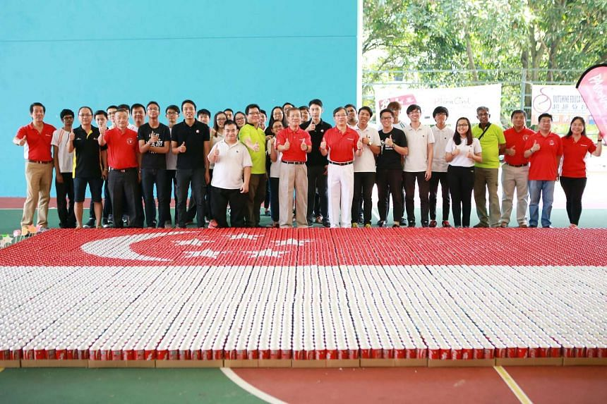 Health Minister Gan Kim Yong (centre, left, in red) posing with volunteers and the PAssionarts Festival event committee with an art installation made with 7,766 recycled aluminium cans showing the Singapore flag.