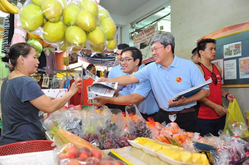 The Workers' Party Png Eng Huat handing a resident a copy of the party's newsletter in Chong Pang on Aug 16, 2015.