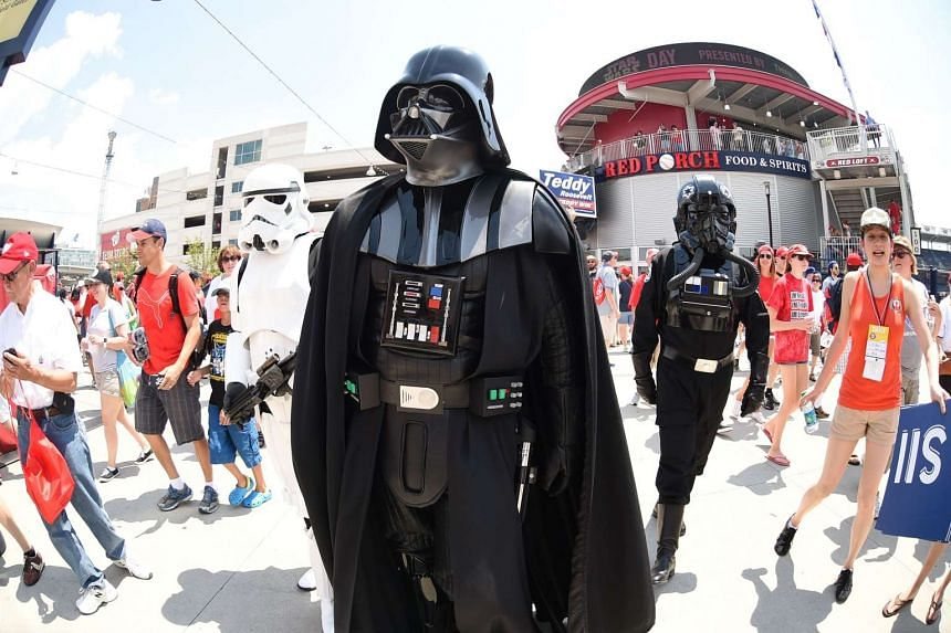 Darth Vader and other Star Wars characters mingle with fans at a US baseball game.